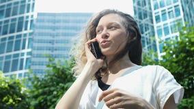 Empresaria que habla en el teléfono en el fondo de altos centros de negocios modernos almacen de metraje de vídeo