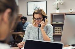 Empresaria que habla en el teléfono en la oficina foto de archivo