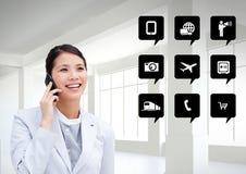 Empresaria que habla en el teléfono móvil al lado de iconos del uso Foto de archivo
