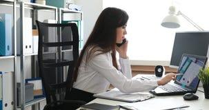 Empresaria que habla en smartphone y que trabaja en el ordenador portátil en oficina moderna metrajes