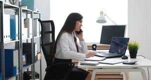Empresaria que habla en smartphone y que trabaja en oficina moderna metrajes