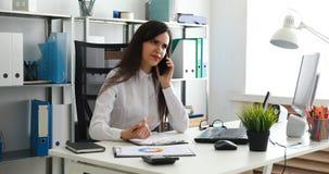 Empresaria que habla en smartphone y que trabaja en oficina moderna almacen de metraje de vídeo