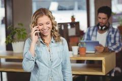 Empresaria que habla sobre el teléfono en oficina Imágenes de archivo libres de regalías