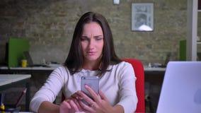 Empresaria que habla vía videochat usando su smartphone en la oficina y la sonrisa almacen de metraje de vídeo