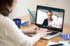 Empresaria que hace la llamada video al hombre de negocios que muestra el documento imagen de archivo