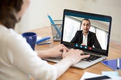 Empresaria que hace la llamada video al socio comercial que usa el ordenador portátil foto de archivo