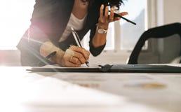 Empresaria que hace las notas que se colocan en su escritorio en oficina fotografía de archivo libre de regalías