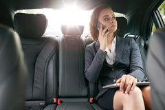 Empresaria que hace una llamada de teléfono mientras que viaja al trabajo Imagen de archivo