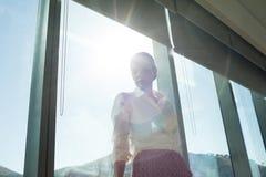 Empresaria que hace una pausa la ventana brillantemente encendida en oficina Fotos de archivo