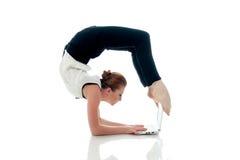 Empresaria que hace yoga y que mecanografía en netbook Imagenes de archivo
