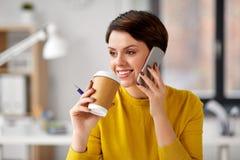 Empresaria que invita a smartphone en la oficina foto de archivo