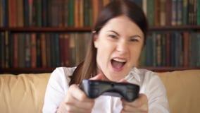 Empresaria que juega a los videojuegos en casa Jugador adicto con el control remoto de la videoconsola metrajes