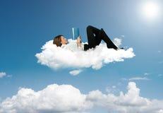Empresaria que lee un libro en una nube foto de archivo
