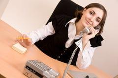 Empresaria que llama por el teléfono en la oficina imagen de archivo
