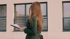 Empresaria que lleva a cabo documentos y que camina a lo largo del edificio de oficinas metrajes