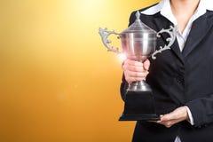 Empresaria que lleva a cabo el premio del trofeo para el éxito en negocio oro fotos de archivo