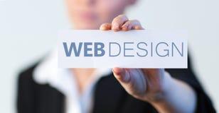 Empresaria que lleva a cabo una etiqueta con el diseño web escrito en él Imagen de archivo libre de regalías