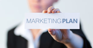 Empresaria que lleva a cabo una etiqueta con el plan de márketing escrito en él Foto de archivo libre de regalías