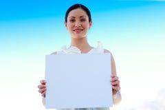 Empresaria que lleva a cabo a una tarjeta en blanco Fotos de archivo libres de regalías