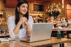 Empresaria que lleva en la camisa que se sienta en café en la tabla, mirando la ventana y la sonrisa En el escritorio es el orden Fotos de archivo