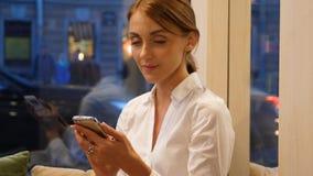 Empresaria que manda un SMS en el smartphone, sentándose en café de la ciudad almacen de video