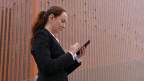 Empresaria que manda un SMS en smartphone en el downown contra el edificio highrise almacen de video