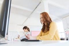 Empresaria que manda un SMS en smartphone en la oficina foto de archivo
