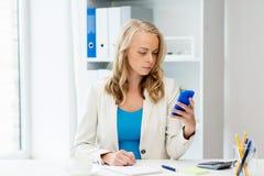 Empresaria que manda un SMS en smartphone en la oficina Imágenes de archivo libres de regalías