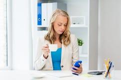 Empresaria que manda un SMS en smartphone en la oficina Foto de archivo libre de regalías