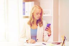 Empresaria que manda un SMS en smartphone en la oficina Fotos de archivo