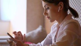 Empresaria que manda un SMS en smartphone usando earpods almacen de video