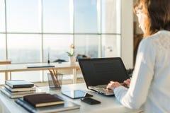 Empresaria que mecanografía en el ordenador portátil en la mujer del lugar de trabajo que trabaja en teclado de la mano de Minist Foto de archivo