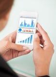 Empresaria que mira cartas financieras en smartphone imagen de archivo libre de regalías