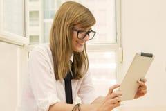 Empresaria que mira el dispositivo de la tableta Imágenes de archivo libres de regalías