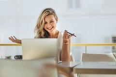 Empresaria que mira el ordenador portátil y que sonríe en el café fotografía de archivo