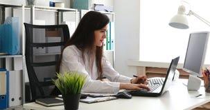 Empresaria que mira en documentos y que trabaja en el ordenador portátil en oficina moderna metrajes