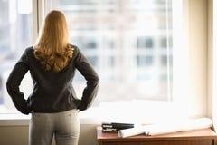 Empresaria que mira hacia fuera la ventana Imagenes de archivo