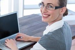 Empresaria que mira la cámara con los vidrios y que usa el ordenador portátil Foto de archivo libre de regalías