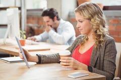 Empresaria que mira la tableta digital en oficina Imagen de archivo libre de regalías