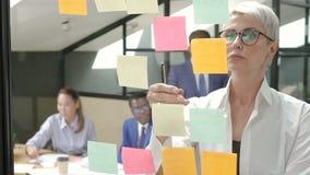 Empresaria que mira a las notas pegajosas que piensan profundamente en sala de reunión de la oficina almacen de video