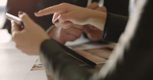 Empresaria que muestra la declaración de las ventas con el colega masculino sobre la tableta digital almacen de metraje de vídeo