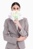 Empresaria que oculta su cara detrás de billetes de banco Imagen de archivo