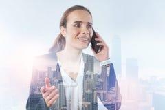 Empresaria que parece confundida mientras que habla en el teléfono Imágenes de archivo libres de regalías