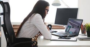 Empresaria que pone la taza a un lado y que pone la cabeza en el ordenador portátil almacen de metraje de vídeo