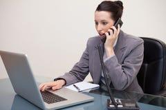 Empresaria que pulsa en la computadora portátil mientras que habla en el teléfono Imagen de archivo libre de regalías