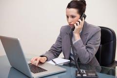 Empresaria que pulsa en su computadora portátil mientras que en el teléfono Foto de archivo libre de regalías