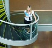 Empresaria que recorre encima de las escaleras en oficina Imágenes de archivo libres de regalías