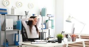 Empresaria que saca los vidrios y que estira, documentos de relleno en oficina moderna almacen de video