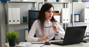Empresaria que saca los vidrios y que mira en la cámara, trabajando en el ordenador portátil en oficina moderna metrajes
