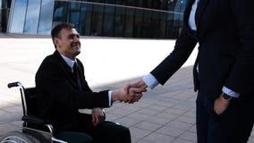 Empresaria que sacude las manos con el hombre de negocios discapacitado al aire libre almacen de metraje de vídeo